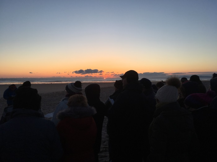 The sun begins to rise at the Easter Sunday Sunrise Service 2018, Lossiemouth, Moray